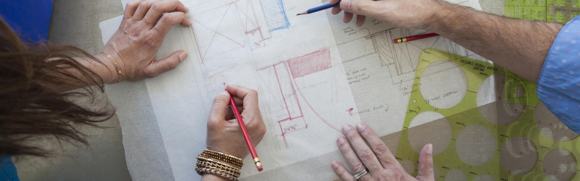 people drawing blueprints
