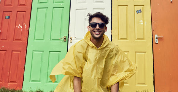 man in raincoat in front of colored doors