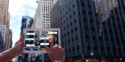 person holding tablet in front of skyscraper