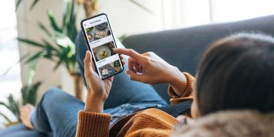 Person laying on couch with phone in-hand, browsing food delivery