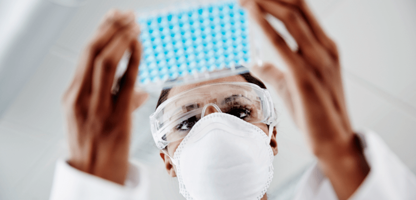 Doctor wearing mask and goggles holding a tray of vials