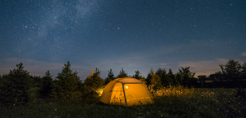 Tent in a forrest clearing at night