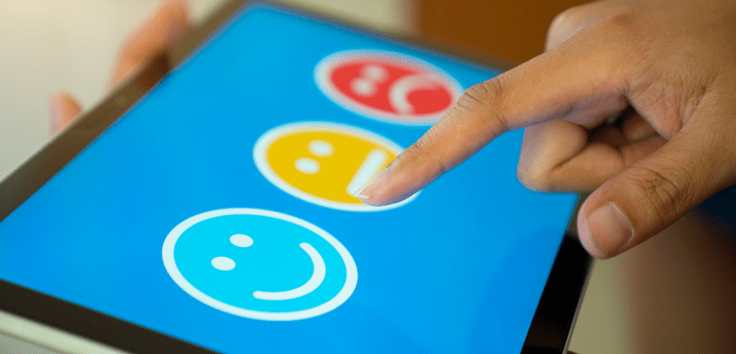 Person touching a digital screen with three smiley face icons