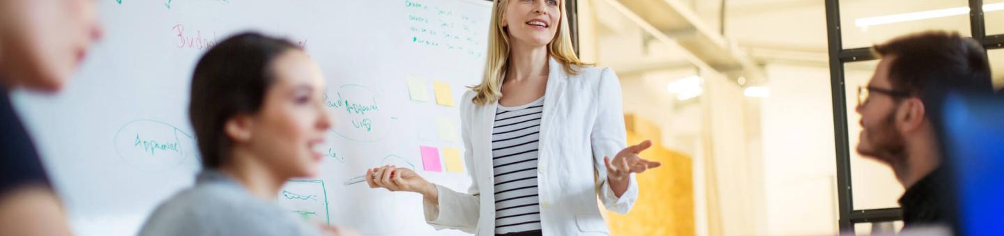 Female executive standing at whiteboard in front of coworkers